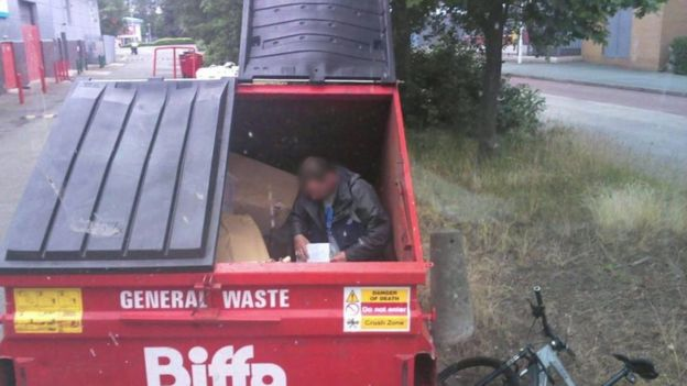 Homeless man sitting inside Biffa recycling bin