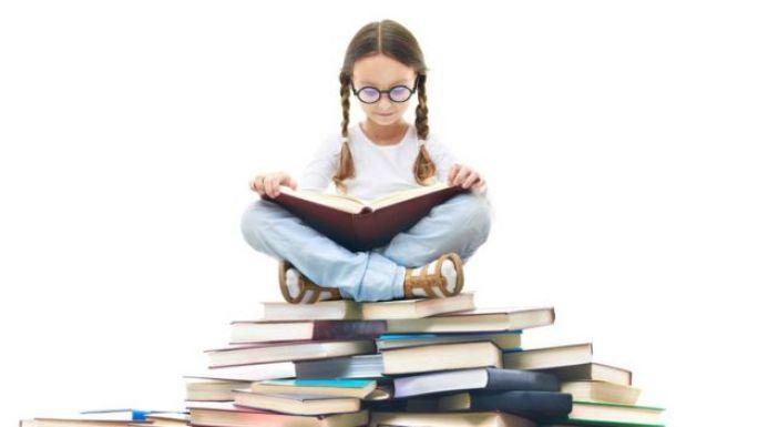 niña sentada sobre un montón de libros