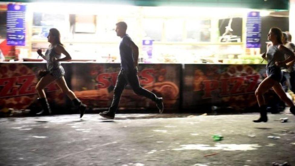 Pessoas correndo da cena do tiroteio.
