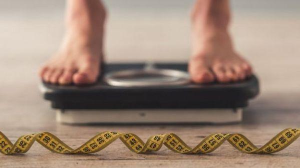 Homem se pesa na balança