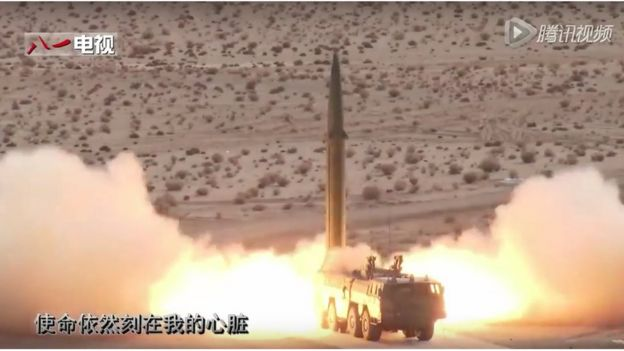 Large missile is launched from a mobile rocket launcher, parked in scrubland
