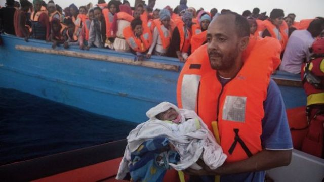 A man carries his five-day-old son after been rescued from a crowded wooden boat as they were fleeing Libya, during a rescue operation at the Mediterranean sea, about 13 miles north of Sabratha, Libya, Monday 29 August 2016