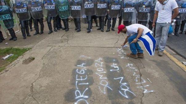 Un hombre pinta una consigna comparando a Ortega y Somoza.