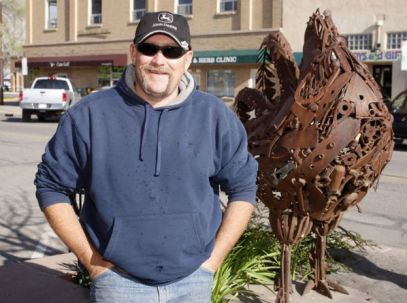 Troy Waters stands next to a statue of Mike in Fruita