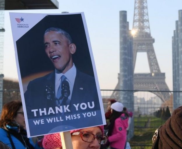 A demonstrator carries a sign featuring former U.S. President Barack Obama during a rally in solidarity with supporters of the Women's March in Washington and many other cities on 21 January 2017 in front of the Eiffel Tower in Paris, one day after the inauguration of the US President Donald Trump