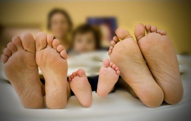 Primer plano de los pies de un hombre, un niño y una mujer en la cama.