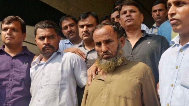 Plain-clothes policemen present two Indian men (bottom 2nd R and 2nd L), who they said are accused of spying for Pakistan, before the media inside the police headquarters in New Delhi, India, October 27, 2016.
