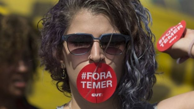 A supporter of Dilma Rousseff, her mouth covered with a sticker that reads in Portuguese;