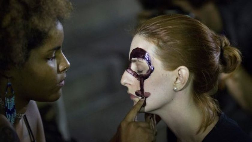 Women paint their faces with female gender symbols for a protest against the gang rape of a 16-year-old girl in Rio de Janeiro, Brazil, Friday, 27 May 2016.