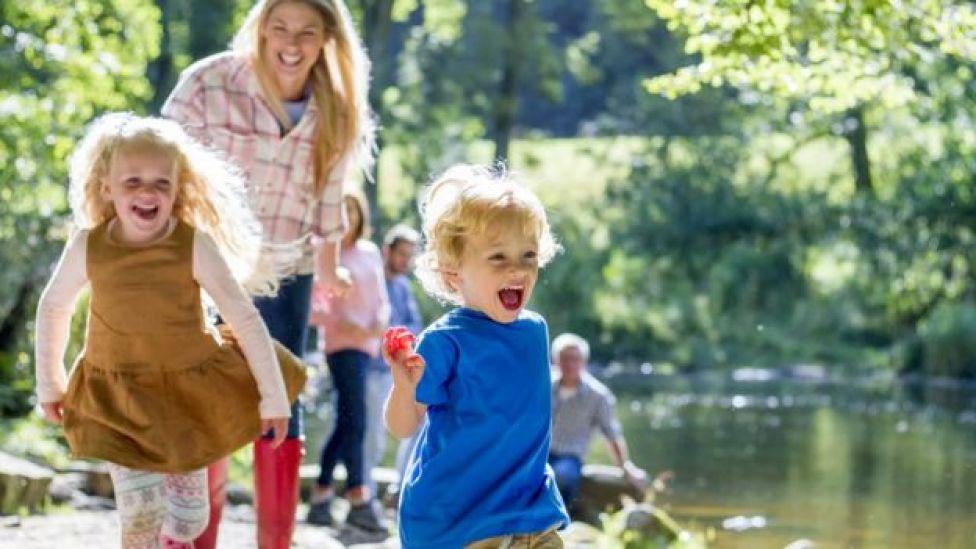 Niños y su madre sonrientes se divierten cerca de un río