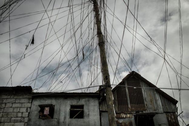 Un hombre asoma la cabeza de su pequeña ventana bajo las enredadas líneas eléctricas en el área de Parola, distrito de Tondo, Manila.