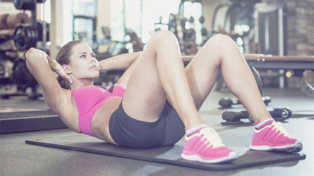 Mujer haciendo abdominales en un gimnasio.