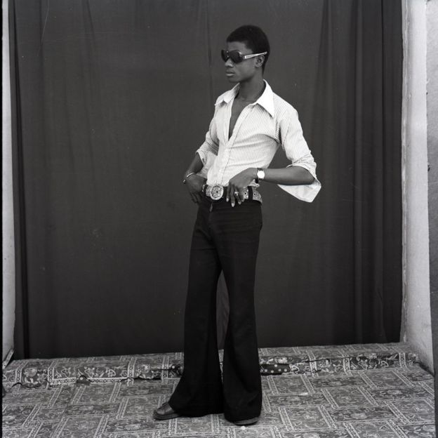 Man wearing flares and sunglasses stands with his hands on his hips