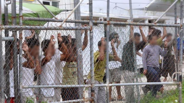 Asylum-seekers behind a fence at the Manus Island detention centre, Papua New Guinea, 21 March 2014