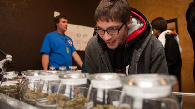 A man selects marijuana strains to purchase at the 3-D Denver Discrete Dispensary on January 1, 2014 in Denver, Colorado