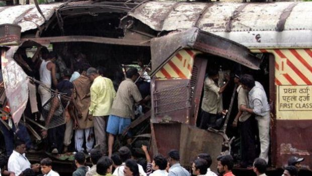 Rescue workers search for bodies inside the mangled compartment of one of the blast affected local trains at Mahim railway station in Mumbai, 11 July 2006.