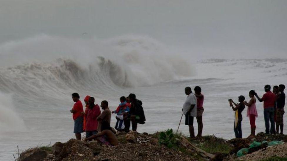 Jamaiquinos observan el oleaje que provocaba el huracán Matthew