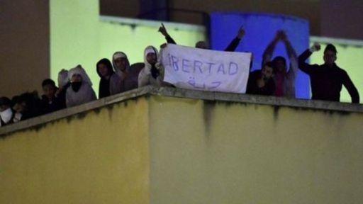 Internos en la azotea del centro de internamiento de extranjeros en Aluche, Madrid, con una pancarta que reza
