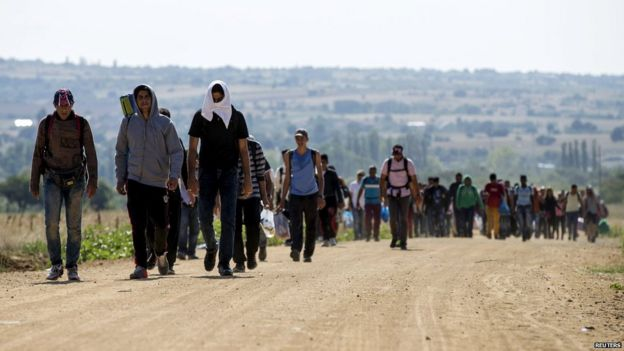 Syrian migrants walk along a road in Serbia