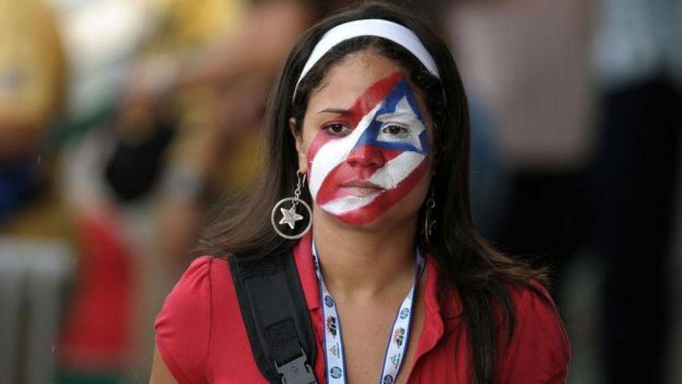 Mujer con la cara pintada con la bandera de Puerto Rico.