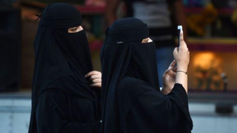 Mulheres sauditas de burca e com celular na mão