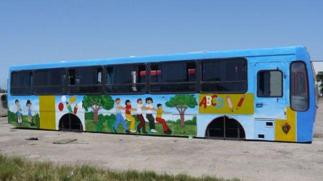 Exterior de uma sala-ônibus, pintada com temática infantil e sem rodas