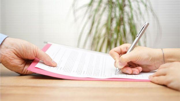 Una mujer firmando un contrato