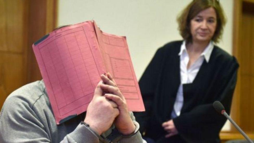 Niels H. durante su juicio, con la cara tapada con una libreta.