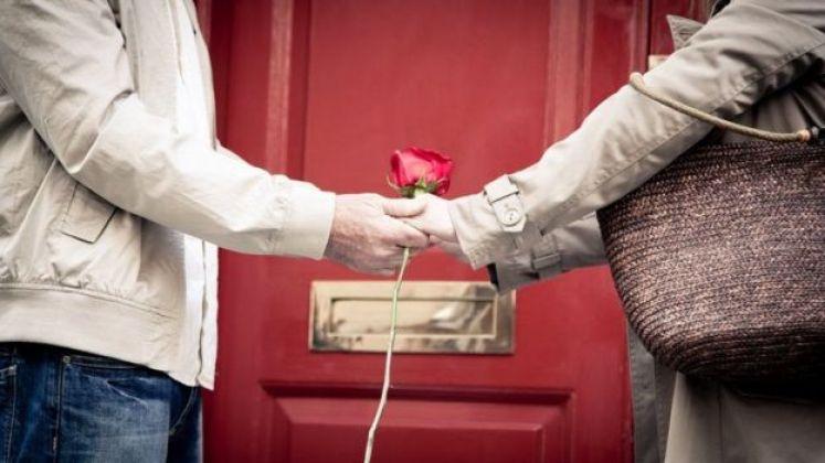 رجل وامرأة يمسكان بأيدي بعضهما البعض