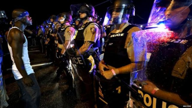 A protester yells at a police line shortly before shots were fired in a police-officer involved shooting in Ferguson, Missouri August 9, 2015.