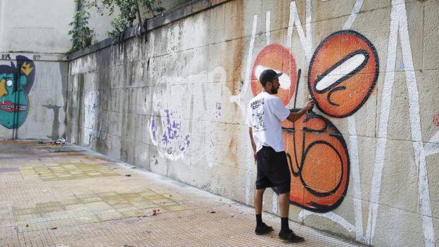 Homem grafita parede no Centro de São Paulo
