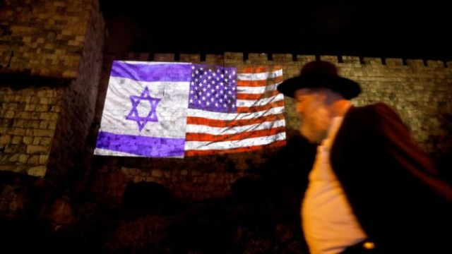 Un hombre camina junto a una proyección de las banderas de Estados Unidos y de Israel sobre el muro de la ciudad antigua de Jerusalén.