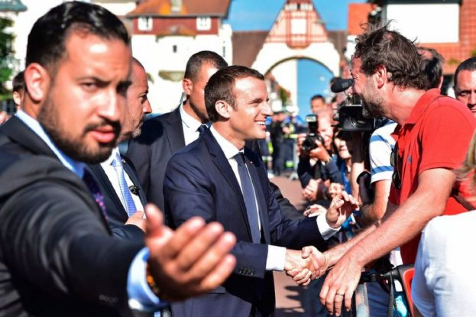 French President Emmanuel Macron (C) shakes hands with people after he voting in Le Touquet, northern France