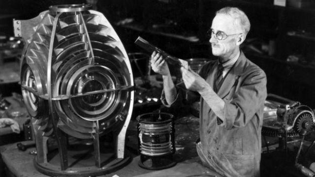 Un utilizado ajusta prismas para formar el lente de un faro.