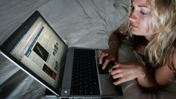 Mulher olha página do Facebook em um notebook