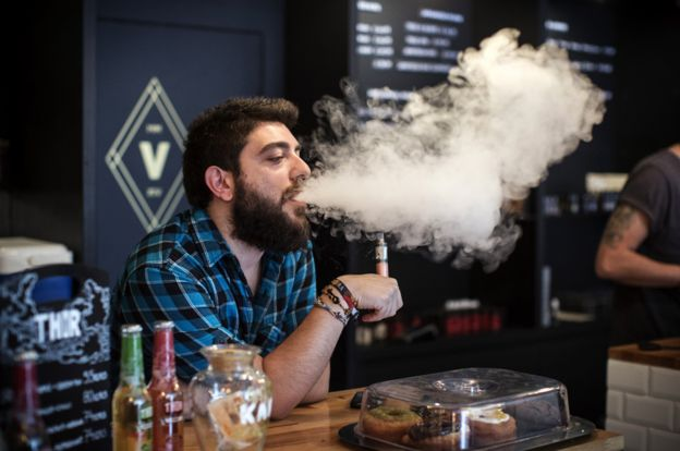 Vape Lab employee uses an e-Cigarette while working
