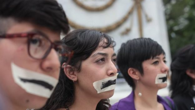 People have their mouths taped as a group of artist, students, journalist and activist stage a protest demanding justice for Ruben Espinosa in Mexico City on 8 August 2015.