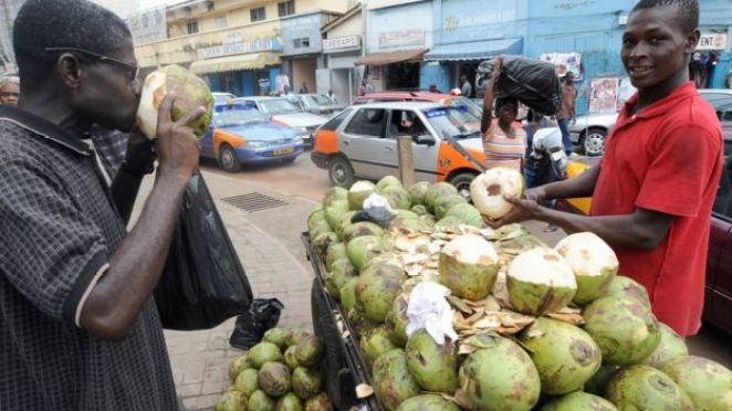 A man drinking coconut water in Accra, Ghana - archive shot