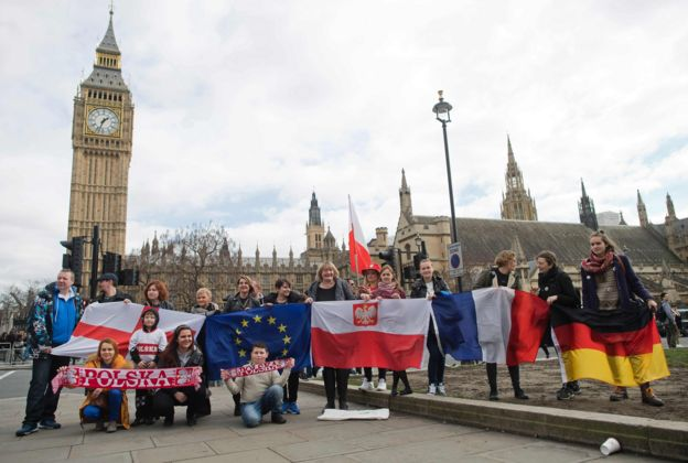 Protestors pose for a photograph with flags from England, European Union, Poland, France and Germany in front of the Elizabeth Tower, better known as