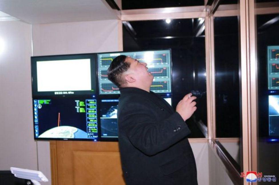 El líder norcoreano, Kim Jong-un fuma un cigarrillo y sonríe. De fondo, unas pantallas parecen mostrar la trayectoria del misil.