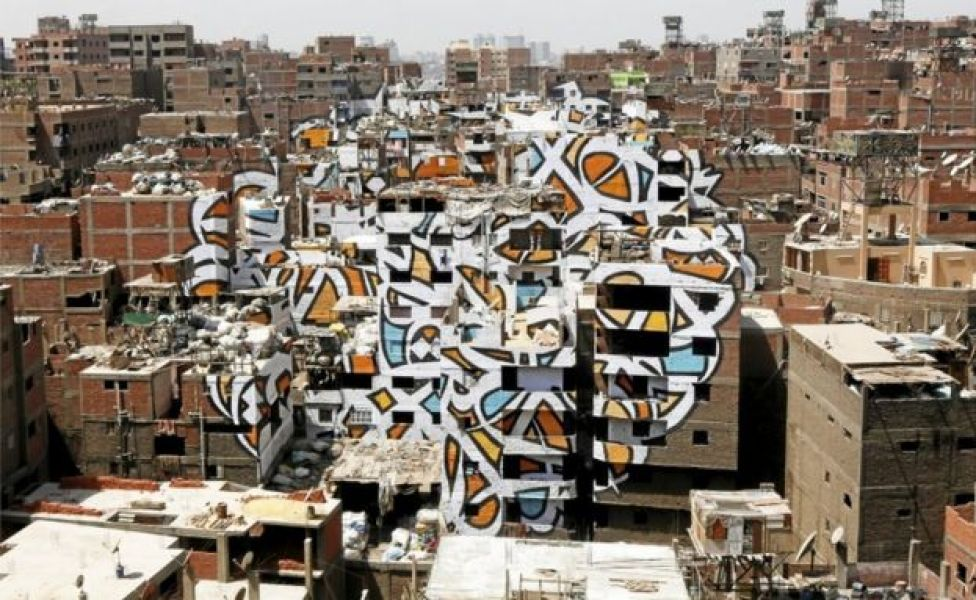 A mural painted on the walls of houses in Zaraeeb, created by French-Tunisian artist El Seed, is pictured in the shanty area known also as Zabaleen or