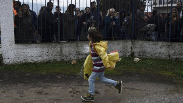 A refugee girl runs as local residents hold a protest outside a school at the Greek village of Profitis some 35 kilometers (22 miles) east of Thessaloniki, on Monday, Oct. 10, 2016.