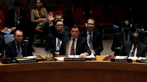 Russian Deputy Ambassador to the United Nations Vladimir Safronkov raises his arm to vote against a United Nations Security Council resolution