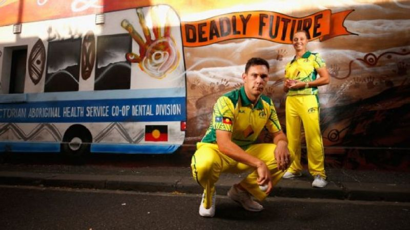 Indigenous cricketers Scott Boland and Ashleigh Gardner in front of an Aboriginal art mural