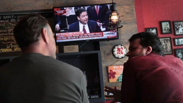 Gente mirando a Comey declarar.