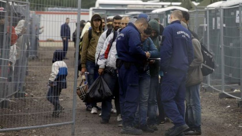 Migrants are checked by police as they arrive at a refugee camp at the Hungarian-Serbian border near Roszke on 11 September 2015