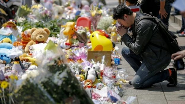 A man offers flowers and prayers a four-year-old child victim of a random killing, at a makeshift memorial at a street next to the crime scene, in Taipei, Taiwan, 29 March 2016.
