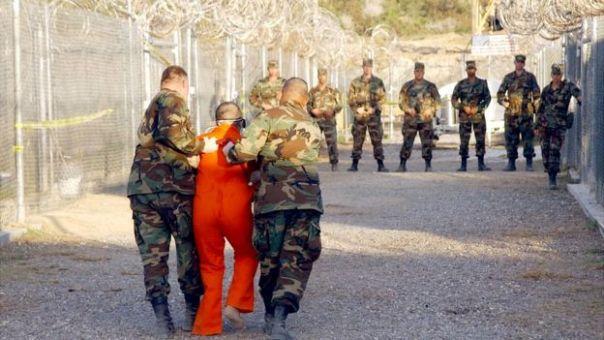 Militares estadounidenses conducen a un preso en Guantánamo.