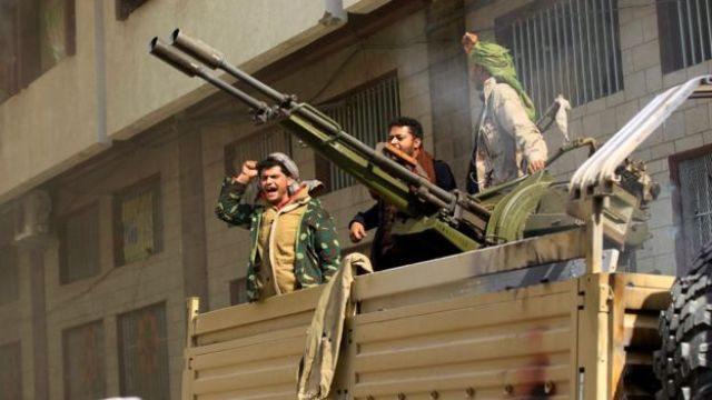 Houthi fighters shout slogans outside the destroyed home of Ali Abdullah Saleh in Sanaa, Yemen (4 December 2017)