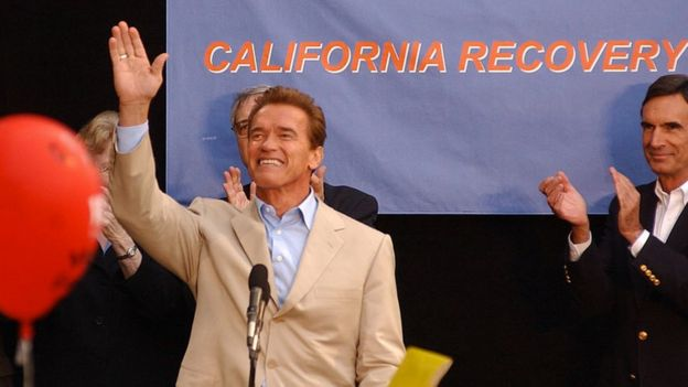 Arnold Schwarzenegger waves at a campaign rally in 2003